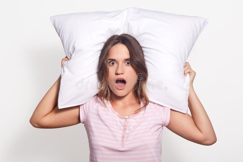 La gente e concetto sano di sonno La donna caucasica abbastanza giovane abbraccia il cuscino molle bianco, chiude gli occhi e gli immagine stock libera da diritti
