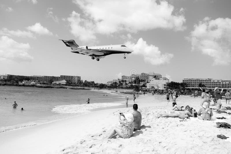 La gente e l'aereo di atterraggio a stMaarten Maho Beach fotografia stock libera da diritti