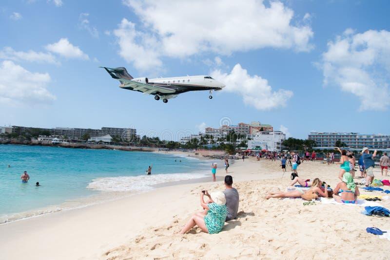 La gente e l'aereo di atterraggio a stMaarten Maho Beach fotografie stock libere da diritti