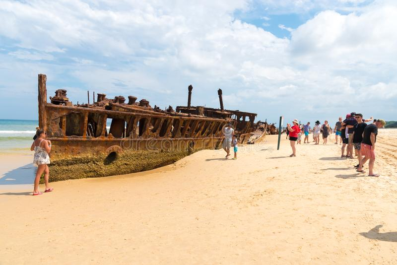 La gente en el Maheno naufraga en la playa de 75 millas, una de las señales más populares en Fraser Island, Fraser Coast, Queensl fotos de archivo libres de regalías