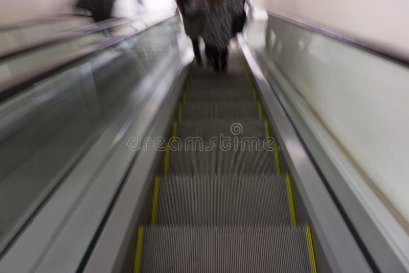 La gente en las escaleras y la escalera móvil móvil en el intercambio coloca cerca de negocio y de centro comercial en París Esce imágenes de archivo libres de regalías