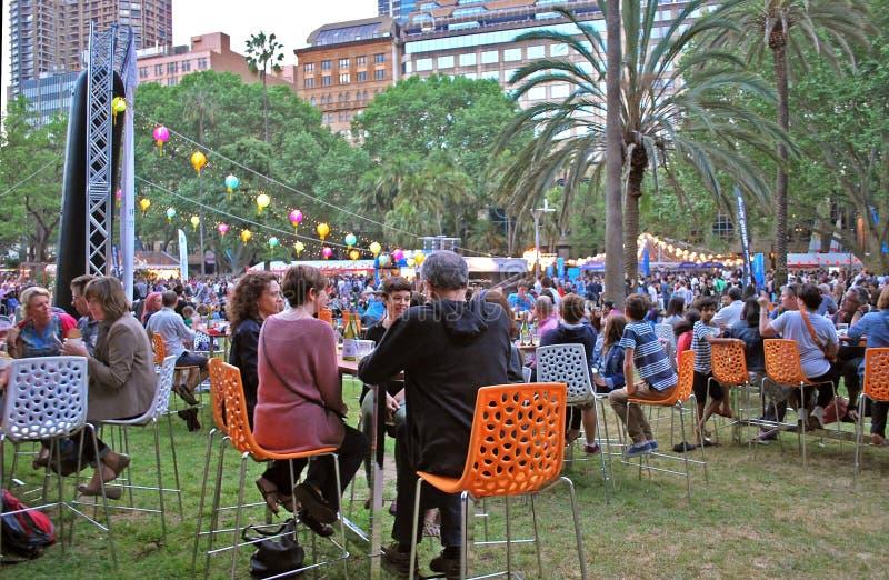 La gente en las tablas está disfrutando de cena y de festividades durante mercado de los tallarines de la noche imagen de archivo