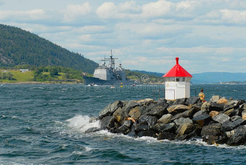 La gente en motoras sigue la nave noruega de los militares en un fiordo en Drobak, Noruega fotografía de archivo