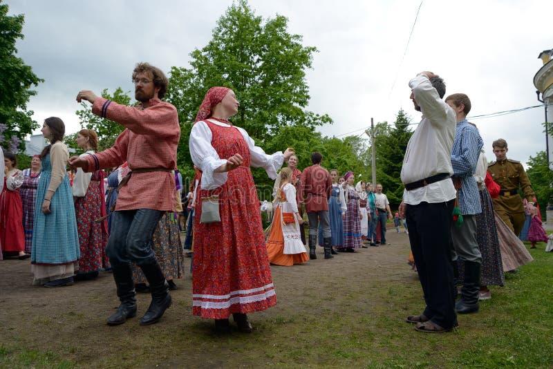 La gente en trajes rusos nacionales está bailando imagenes de archivo