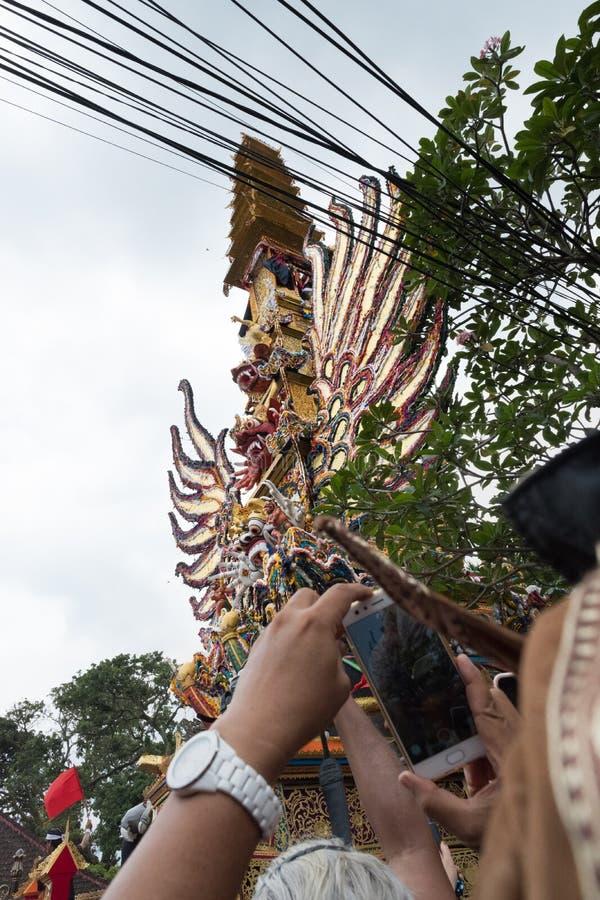 La gente en Ubud, Bali que capturaba la torre de la cremación de la familia real hizo una oferta como se lleva templo al 2 de mar imagen de archivo libre de regalías