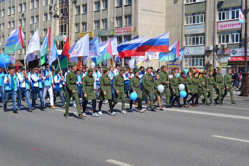 La gente en uniforme con las banderas participa en la demostración en honor fotos de archivo