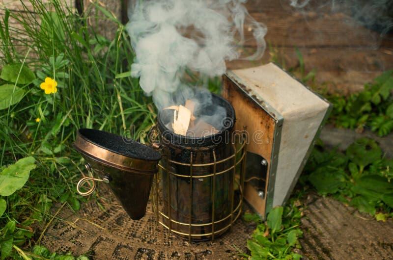 La gente enciende el dispositivo para fumigar las abejas con humo fotografía de archivo