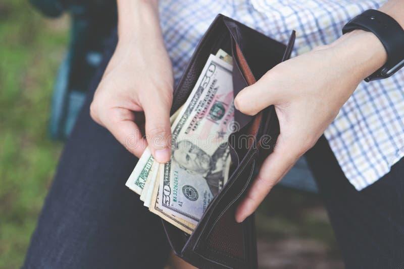La gente equipaggia la seduta tenendo un portafoglio nelle mani del conteggio la diffusione di contanti un uomo per prendere i so fotografia stock libera da diritti