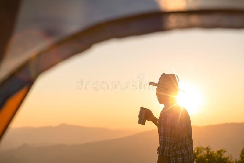 La gente es feliz de sostener una taza de café cerca de la tienda alrededor de la montaña fotografía de archivo libre de regalías