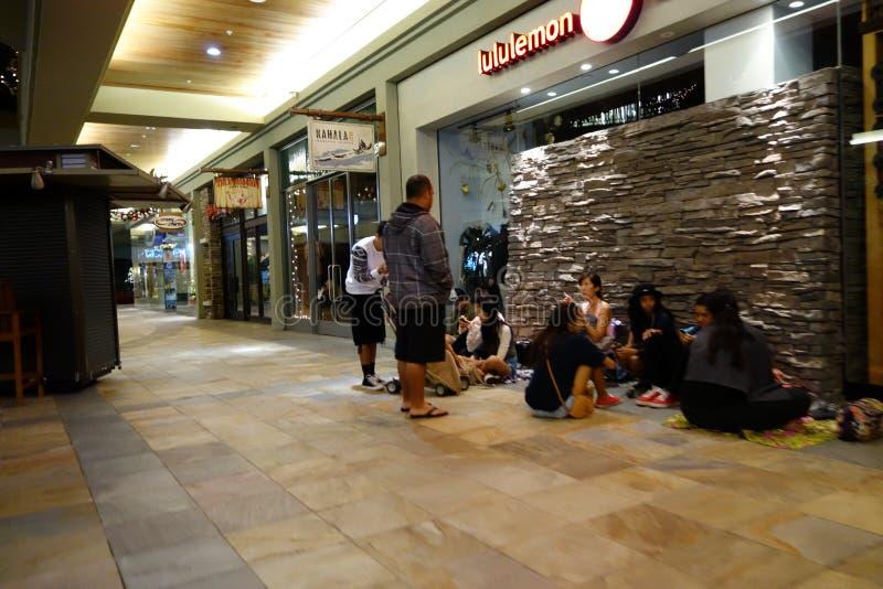 La gente espera en el piso en la cola para la abertura de la tienda de Lululemon foto de archivo