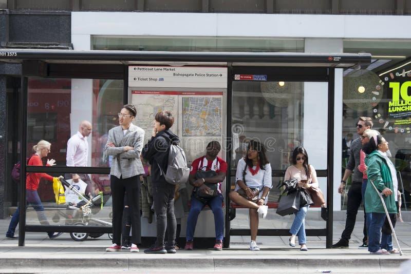 La gente está esperando el autobús en la parada de autobús Los representantes de diversas nacionalidades viven en Londres imagen de archivo libre de regalías