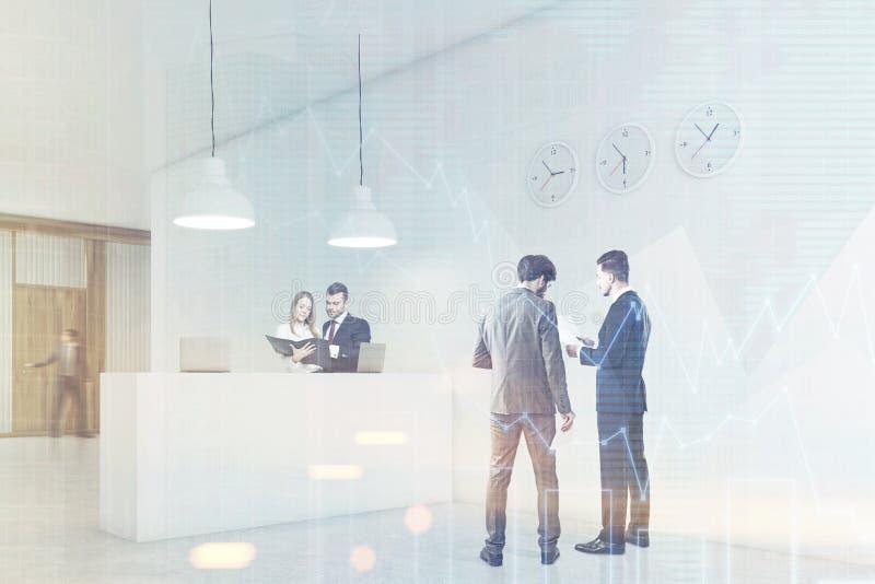 La gente está hablando en un pasillo cerca de contador de la recepción con los relojes imágenes de archivo libres de regalías