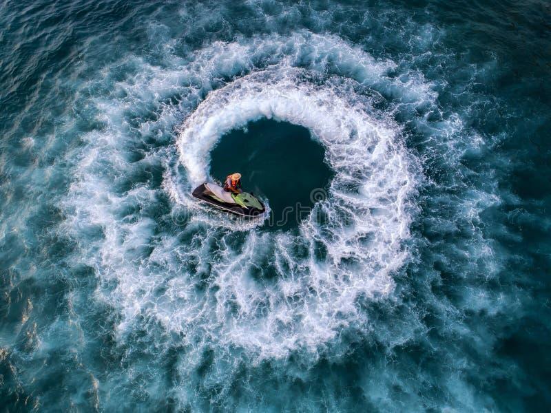 La gente está jugando un esquí del jet en el mar Silueta del hombre de negocios Cowering Visión superior E imagenes de archivo
