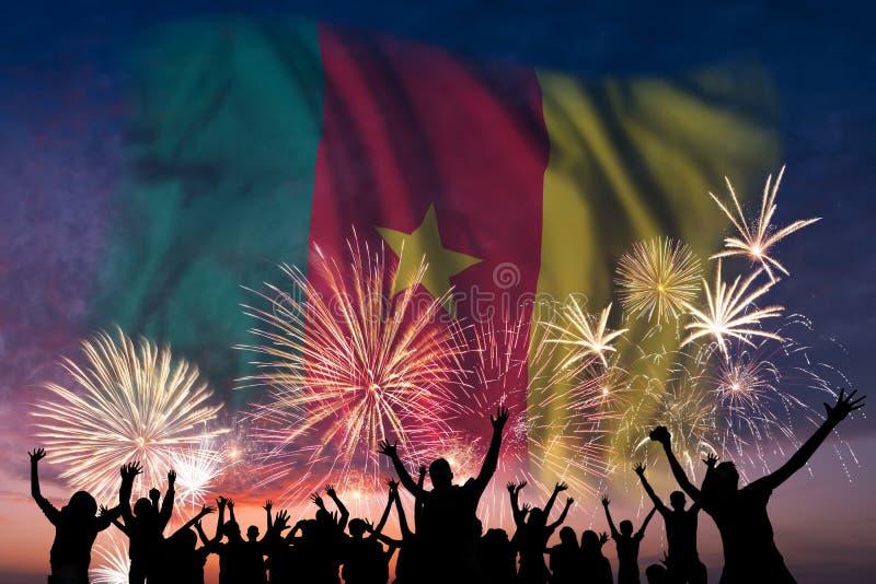 La gente está mirando en los fuegos artificiales y la bandera del Camerún imagen de archivo libre de regalías