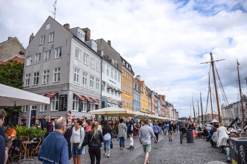 La gente está pasando su tiempo que visita Nyhavn, un distrito muy popular de la costa, del canal y del entretenimiento en Copenh fotos de archivo