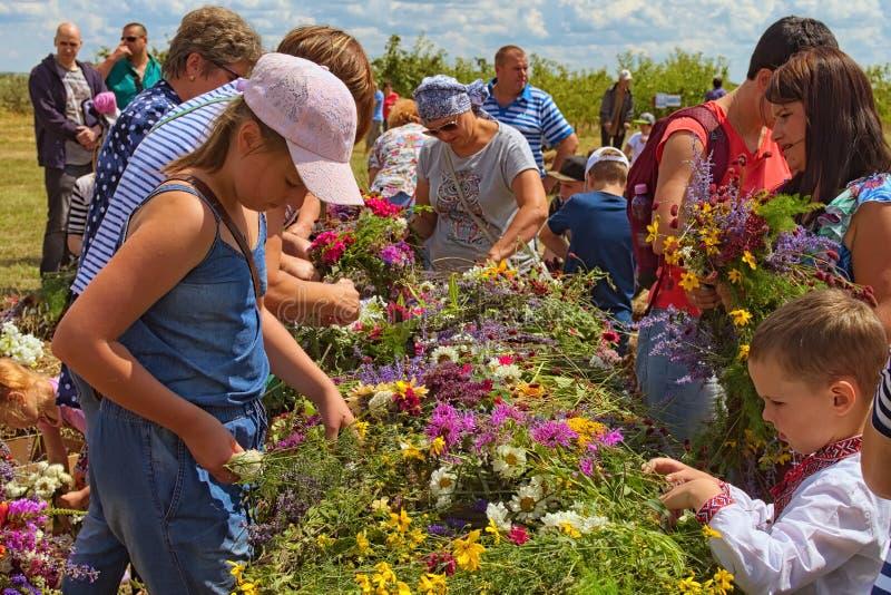 La gente está tejiendo las guirnaldas de las flores salvajes Concepto del verano Tradición ucraniana maravillosa Berry Festival B imágenes de archivo libres de regalías