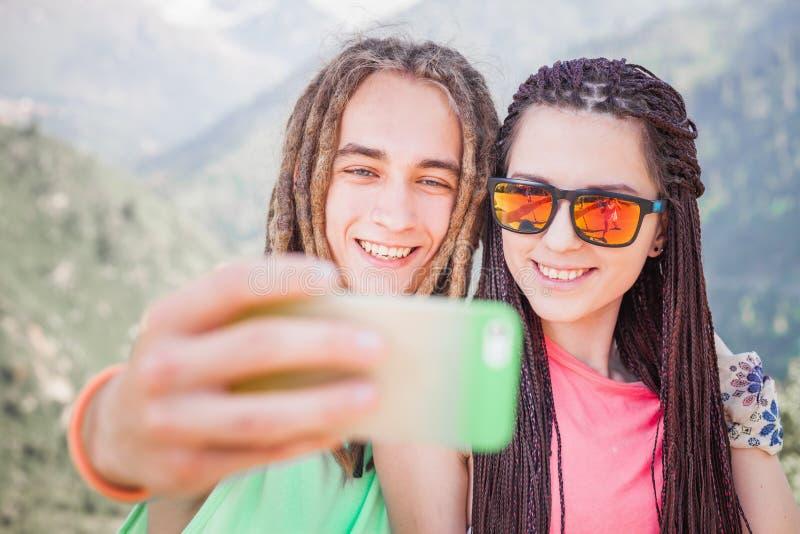 La gente feliz hace el selfie en el teléfono móvil en la montaña al aire libre imagen de archivo
