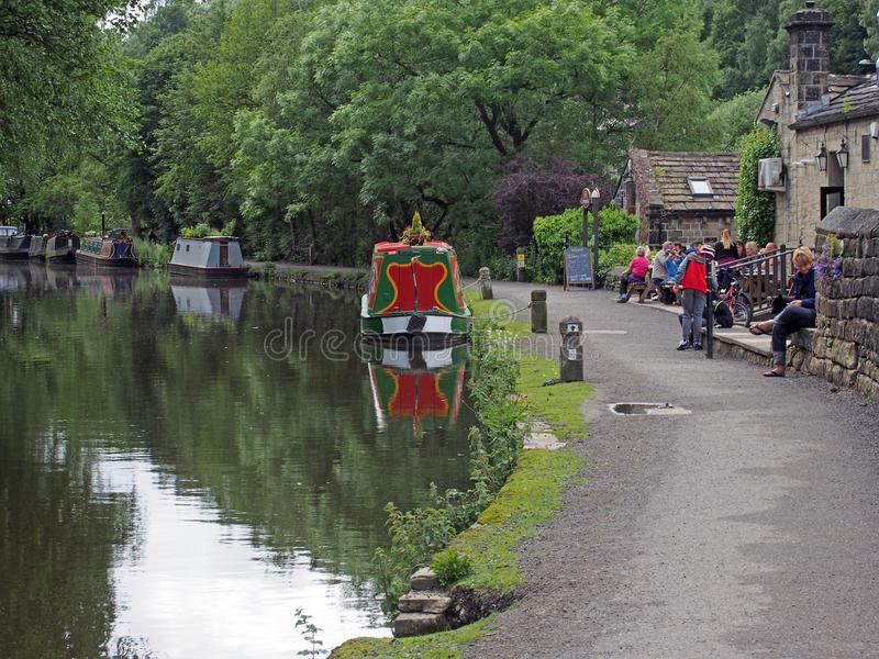 la gente fuori del pub del molo di stubbings sul canale del rochdale dentro hebden il ponte con le chiatte e le case galleggianti immagini stock libere da diritti