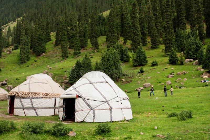 La gente gioca all'aperto vicino alle case Yurts degli agricoltori dell'asiatico in montagne centroasiatiche immagine stock