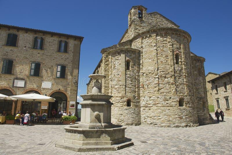 La gente gode del pranzo al quadrato centrale della città medievale di San Leo in San Leo, Italia fotografia stock libera da diritti