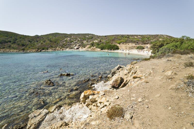 La gente gode di chiara acqua in una baia selvaggia della Sardegna immagini stock libere da diritti