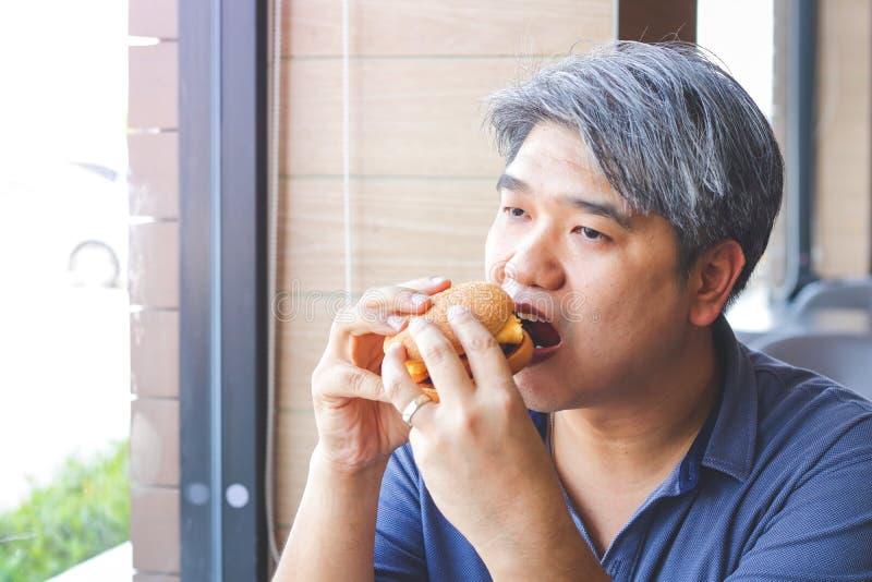 La gente grassa mangia gli hamburger fotografie stock