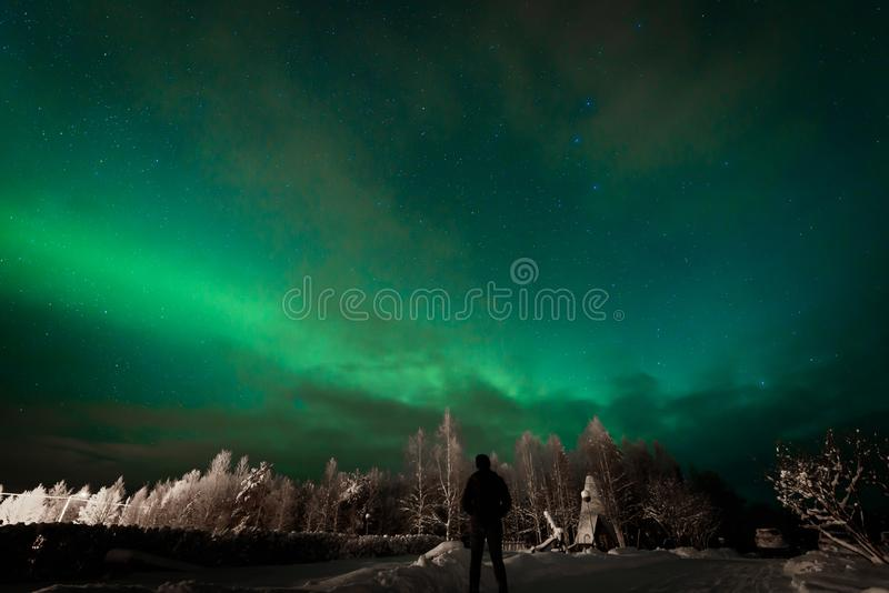 La gente guarda i fari settentrionali di Aurora Borealis sul lago del villaggio di Kuukiuru a Lapland, Finlandia fotografia stock libera da diritti