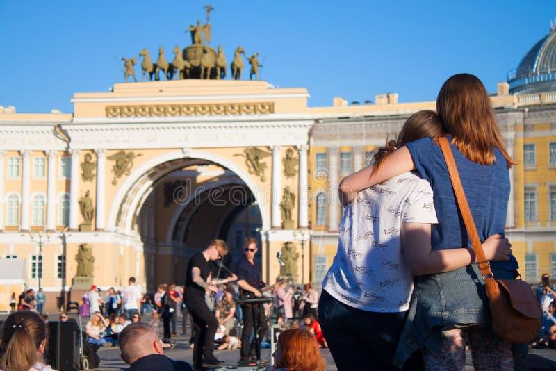 La gente guarda una prestazione dei musicisti della via su PA del centro urbano fotografia stock libera da diritti
