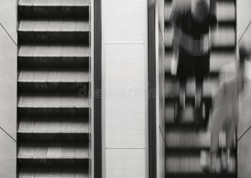 La gente guida sulla scala mobile Esca la metropolitana Esposizione lunga immagini stock libere da diritti