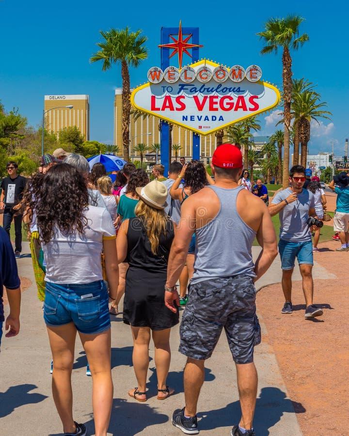 La gente ha allineato su per prendere le loro foto con il benvenuto leggendario al segno favoloso di Las Vegas fotografia stock