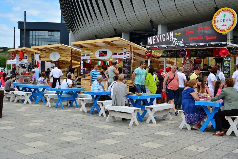 La gente ha uno spuntino al festival dell'alimento della via in Central Park Cluj immagine stock libera da diritti