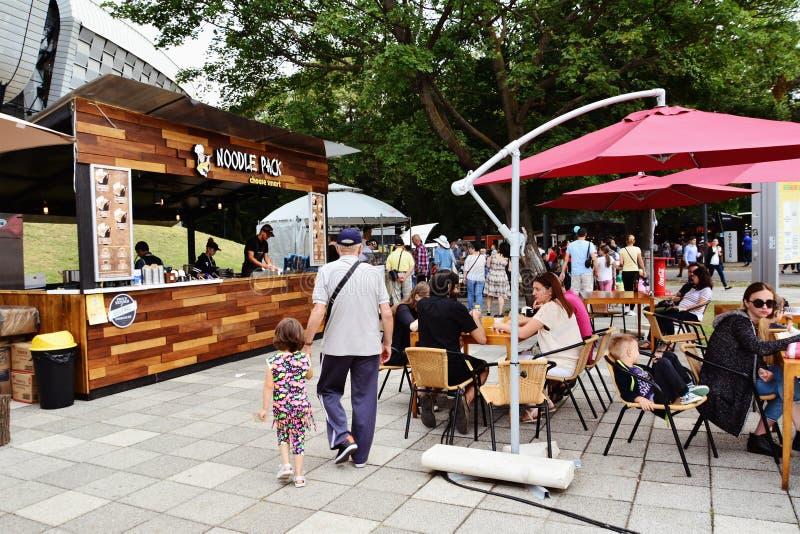 La gente ha uno spuntino al festival dell'alimento della via in Central Park Cluj fotografia stock