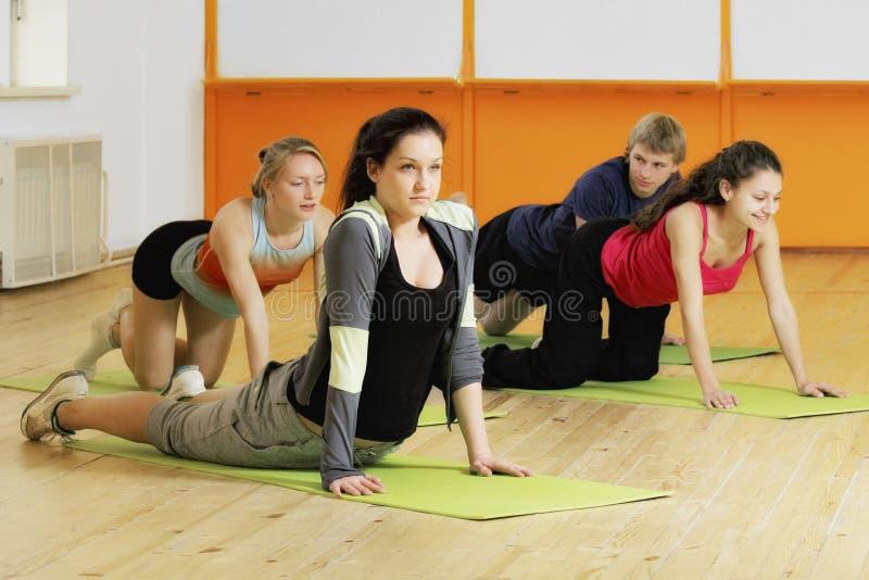 La gente hace ejercicios en piso fotos de archivo