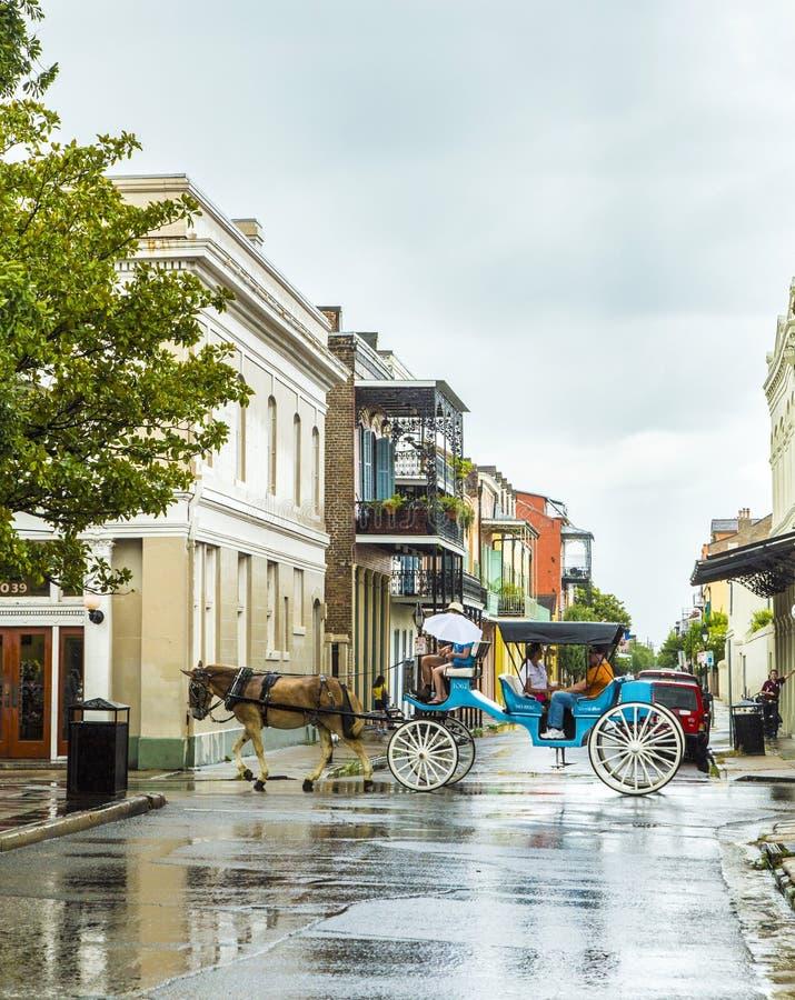 La gente hace un viaje de coche del caballo en el viejo barrio francés imagenes de archivo