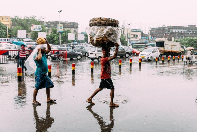 La gente india que camina bajo la lluvia con lleva mercanc?as al tren cerca del ?rea del ferrocarril del empalme de Howrah fotografía de archivo