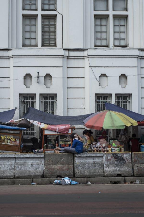 La gente indonesiana cammina dalle stalle dell'alimento della via in una via vicino a Kota a Jakarta, Indonesia immagini stock