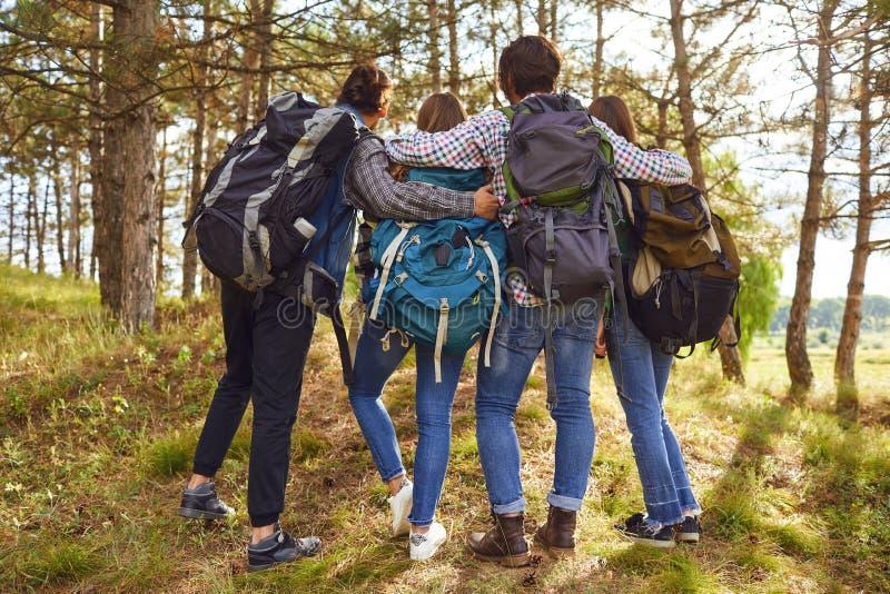 La gente joven con las mochilas se coloca en el bosque de detrás imágenes de archivo libres de regalías