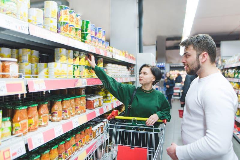 La gente joven con un carro elige verduras conservadas en un supermercado Compras de la familia en la tienda fotografía de archivo