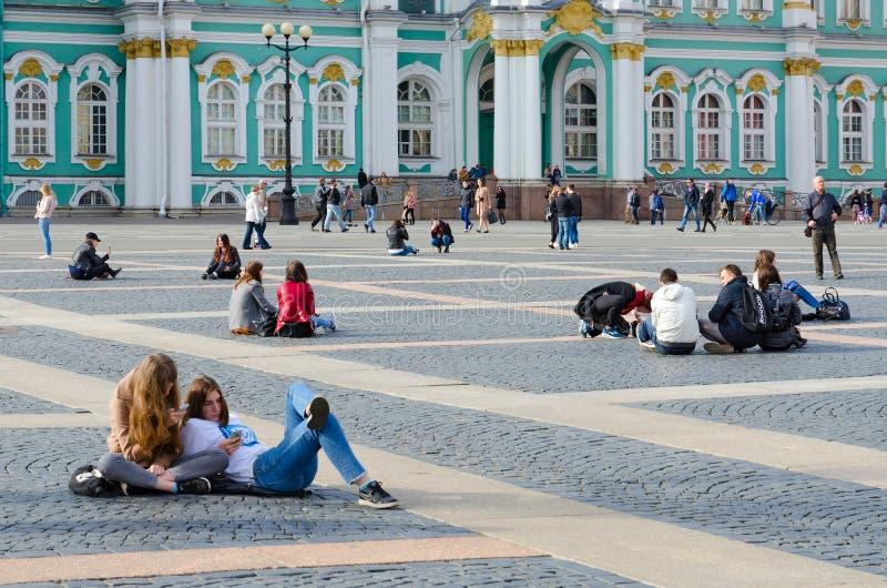 La gente joven descansa sobre el cuadrado del palacio, St Petersburg, Rusia fotografía de archivo