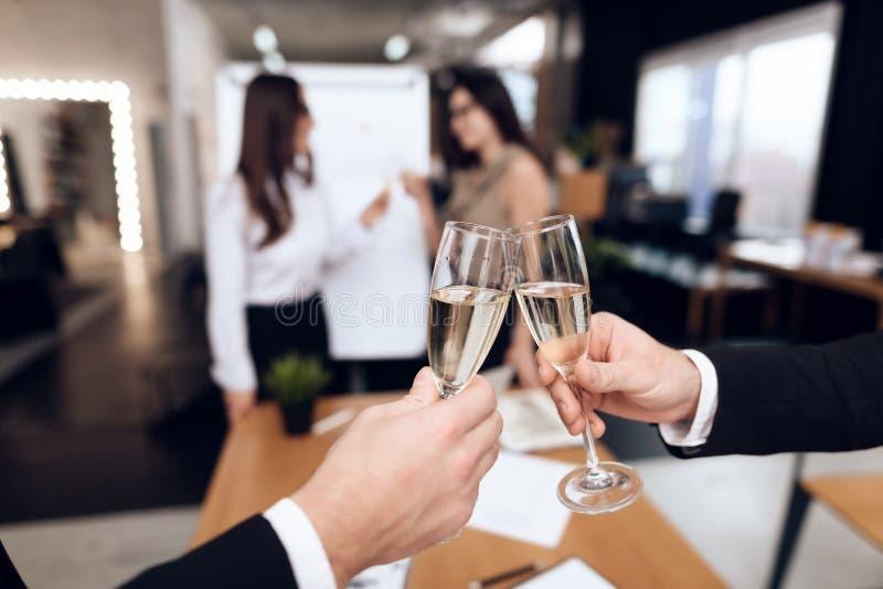 La gente joven en trajes lleva bebidas alcohólicas después de una reunión de negocios imagenes de archivo
