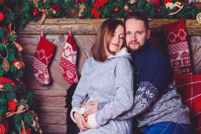 La gente joven feliz se da los regalos por la chimenea cerca del árbol de navidad imagen de archivo