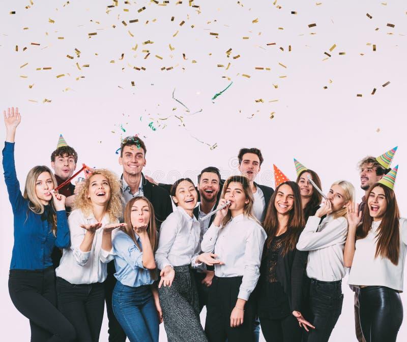 La gente joven sonriente feliz con las cajas de regalo y el partido que sopla silba imagenes de archivo