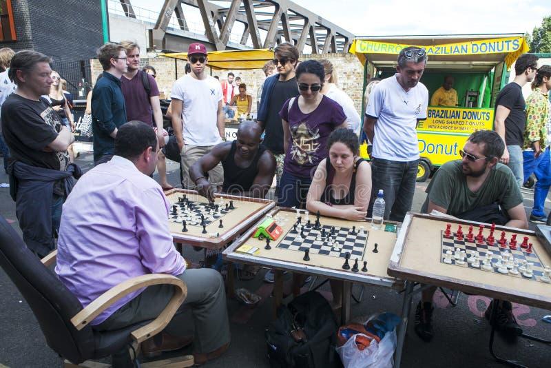 La gente locale non identificata ha giocato gli scacchi alla via del vicolo del mattone immagini stock