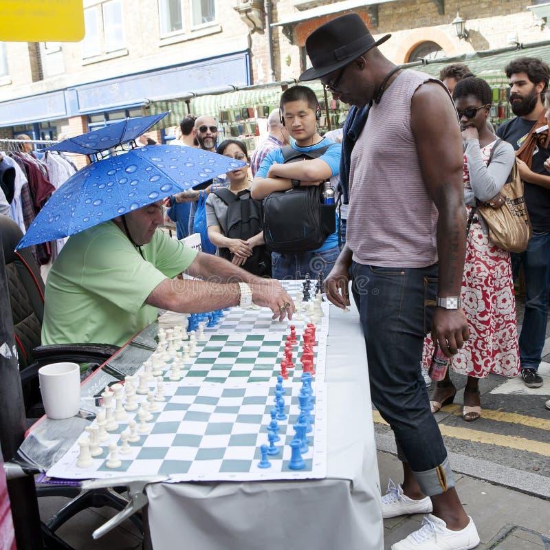 La gente locale non identificata ha giocato gli scacchi alla via del vicolo del mattone a Londra Regno Unito fotografia stock libera da diritti