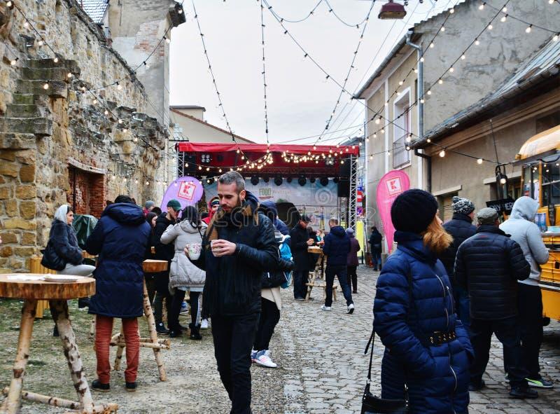 La gente mangia l'alimento della via ed ha una bevanda calda all'edizione dell'inverno di festival dell'alimento della via fotografie stock