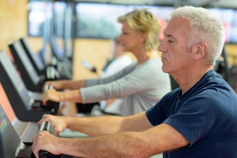 La gente mayor en el gimnasio que hace girar en aptitud bike fotos de archivo