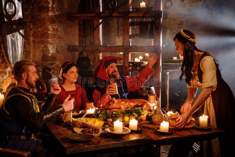 La gente medieval come y bebe en interior antiguo de la cocina del castillo fotografía de archivo libre de regalías