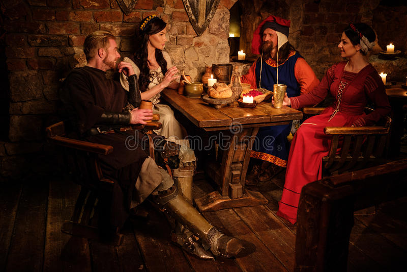 La gente medieval come y bebe en taberna antigua del castillo imagen de archivo libre de regalías