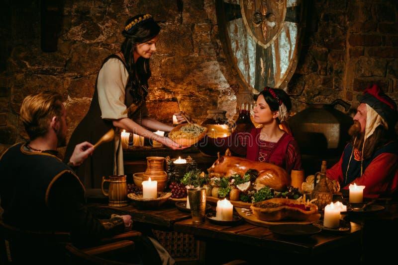 La gente medieval come y bebe en taberna del castillo foto de archivo libre de regalías