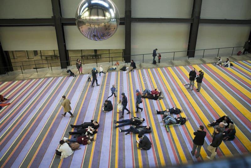 La gente miente en la alfombra en el edificio de la mirada moderna moderna en el péndulo gigante que balancea sobre ella imagenes de archivo